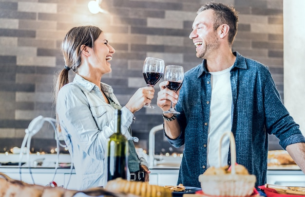 Giovani coppie nell'amore che beve vino rosso alla cucina della casa Foto Premium