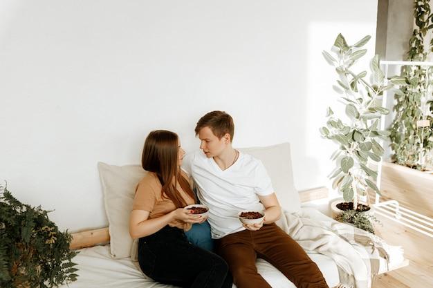 Una giovane coppia innamorata fa colazione insieme a casa in cucina. uomo e donna che mangiano cereale con latte per la prima colazione. Foto Premium