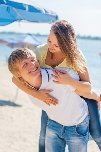 Giovani coppie nell'amore divertendosi e saltando sulla spiaggia Foto Premium