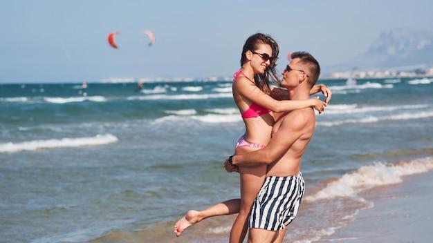 Giovani coppie nell'amore che cammina sulla spiaggia. Foto Premium