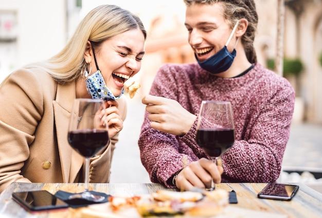 Giovane coppia innamorata di maschere facciali aperte divertendosi al wine bar all'aperto Foto Premium