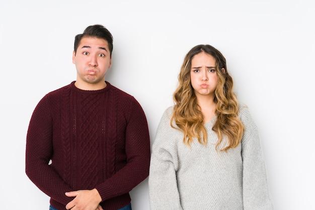 La giovane coppia in posa su sfondo bianco soffia sulle guance, ha un'espressione stanca Foto Premium