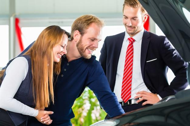 Giovani coppie e venditore con auto nel concessionario auto Foto Premium