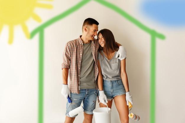 Giovani coppie con i rulli di pittura che abbracciano e che sorridono dopo la verniciatura della parete nella nuova casa Foto Premium