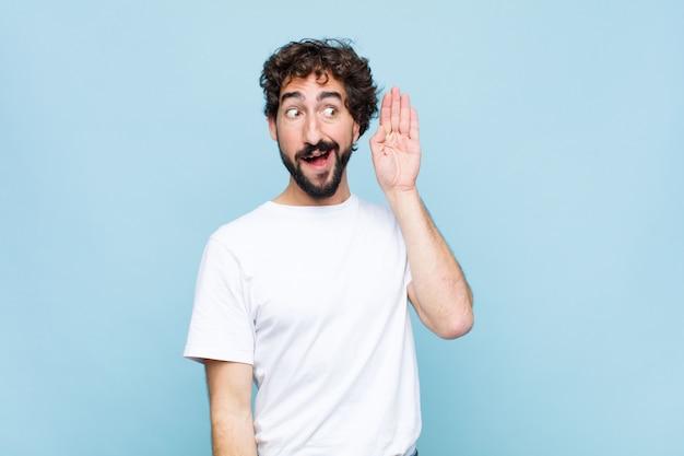 Giovane pazzo uomo barbuto che sorride, guardando curiosamente di lato, cercando di ascoltare pettegolezzi o di sentire un segreto contro la parete piatta Foto Premium