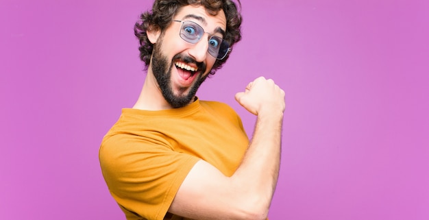 Giovane pazzo che si sente felice, positivo e di successo, motivato quando affronta una sfida o celebra buoni risultati contro la parete piatta Foto Premium