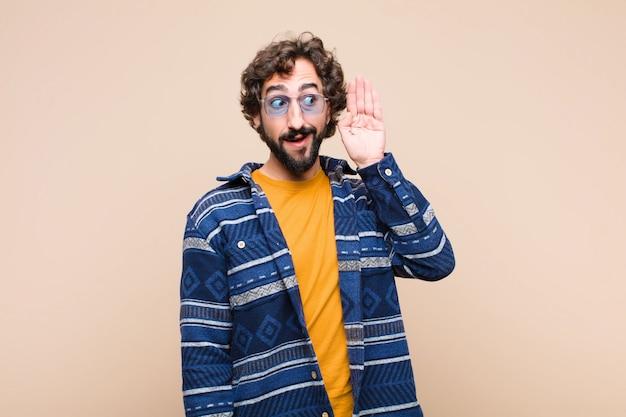 Giovane pazzo figo che sorride, guardando curiosamente di lato, cercando di ascoltare pettegolezzi o di sentire un segreto contro la parete piatta Foto Premium