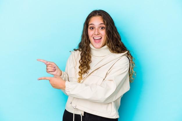 La giovane donna dei capelli ricci ha isolato il puntamento eccitato con gli indici via Foto Premium