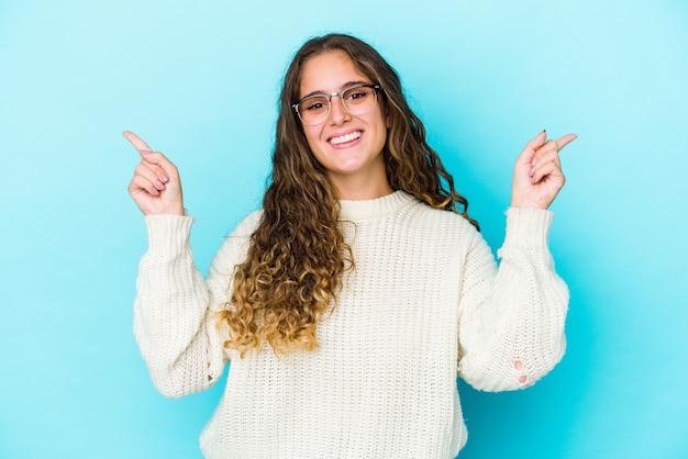Giovane donna capelli ricci isolata che punta a diversi spazi di copia, scegliendo uno di loro, mostrando con il dito Foto Premium