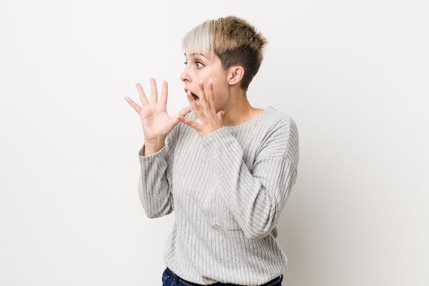 La giovane donna caucasica curvy isolata su priorità bassa bianca grida forte, tiene gli occhi aperti e le mani tese. Foto Premium