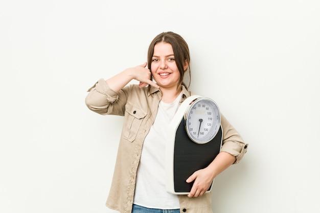 Giovane donna curvy che tiene una scala che mostra un gesto di chiamata di telefono cellulare con le dita. Foto Premium
