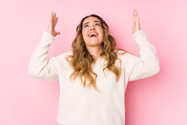 Giovane donna curvy in posa in uno spazio rosa isolato urlando al cielo, guardando in alto, frustrato. Foto Premium