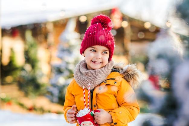 Giovane ragazzo carino in una giacca arancione sulla pista di pattinaggio Foto Premium