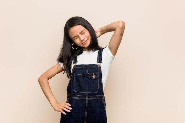 Giovane adolescente cinese carino giovane donna bionda che indossa un cappotto sul dolore al collo sofferenza rosa a causa di uno stile di vita sedentario. Foto Premium