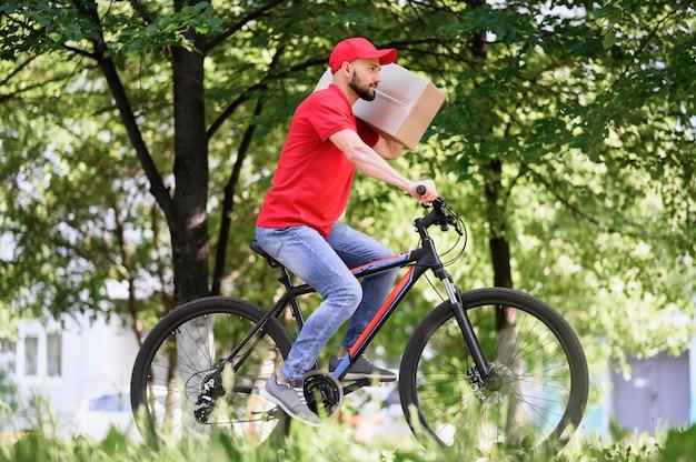 Giovane uomo di consegna in sella a bicicletta con pacco Foto Premium