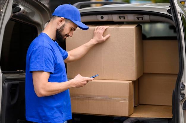 Giovane uomo di consegna che verifica spedizione Foto Premium
