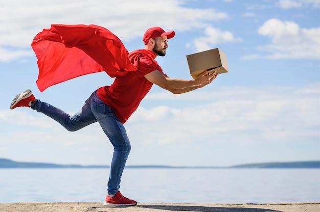 Giovane uomo di consegna che indossa mantello da supereroe Foto Premium
