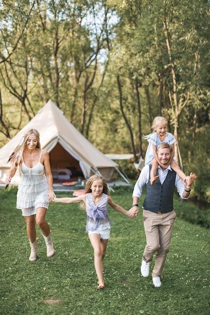 Giovane famiglia in abbigliamento casual boho, papà, mamma e due figlie tenendosi per mano e correndo Foto Premium
