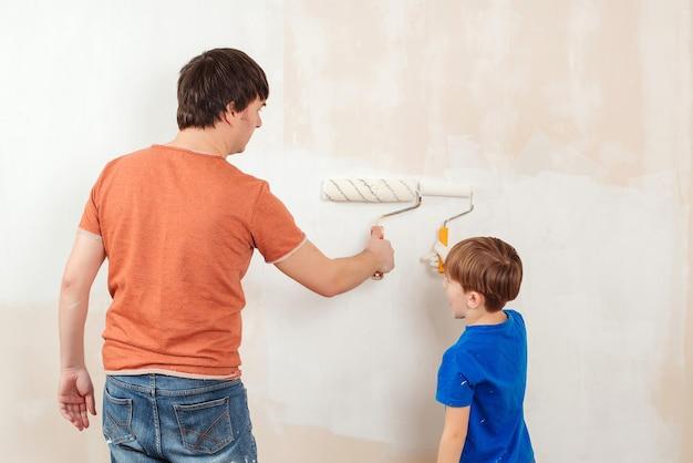 Muro di casa pittura giovane famiglia. padre e figlio che dipingono un muro. Foto Premium