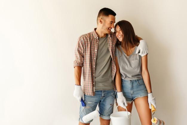 Giovane famiglia con il rullo di vernice che abbraccia e che sorride dopo la verniciatura della parete nella nuova casa Foto Premium