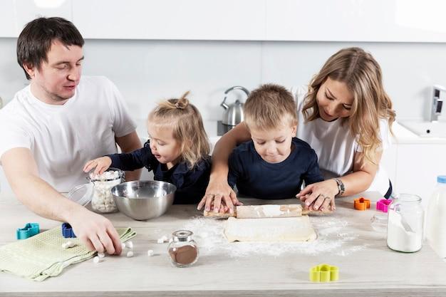 Una giovane famiglia con due bambini piccoli in cucina sta preparando la pasta per biscotti e ride Foto Premium