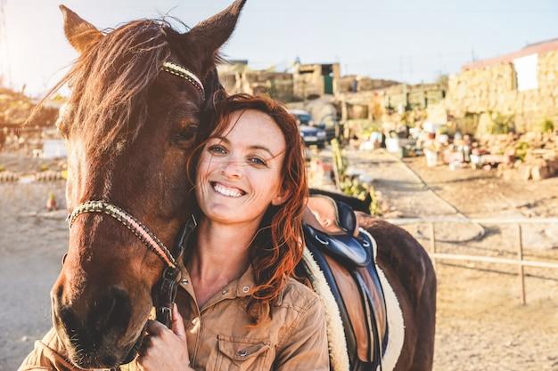 Donna giovane agricoltore che gioca con il suo cavallo in una giornata di sole all'interno del ranch di recinto - concetto di amore tra persone e animali - focus principale sull'occhio degli animali Foto Premium