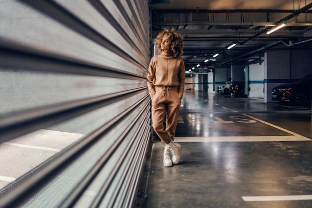 Giovane donna alla moda con i capelli ricci che tengono le mani in tasca mentre si trovava nel garage sotterraneo. Foto Premium