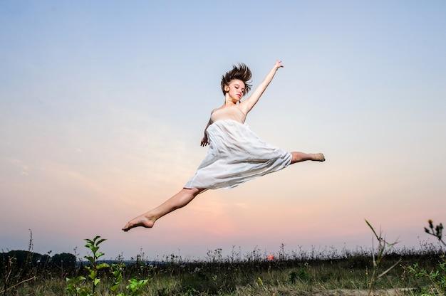 Il giovane ballerino di balletto femminile esegue all'aperto sul tramonto Foto Premium