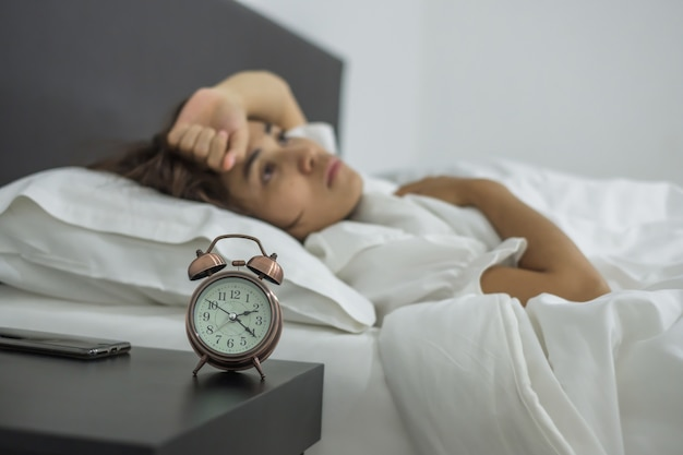 Giovane donna dorme in camera da letto. insonnia che dorme, preoccupata e stressata Foto Premium