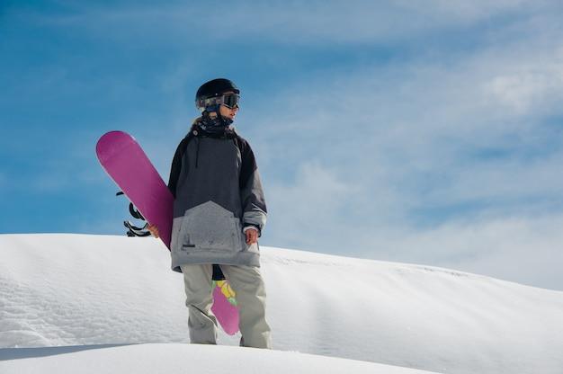 Giovane snowboarder femminile che sta sul pendio di montagna Foto Premium