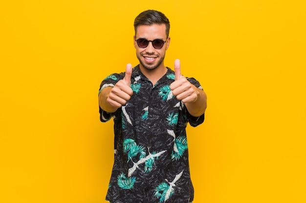 Giovane uomo filippino che indossa abiti estivi con il pollice in alto, applausi per qualcosa, supporto e concetto di rispetto. Foto Premium