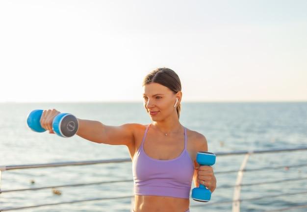 La donna adatta dei giovani pratica i pugni con le teste di legno sulla spiaggia all'alba. allenamento mattutino con pesi liberi Foto Premium