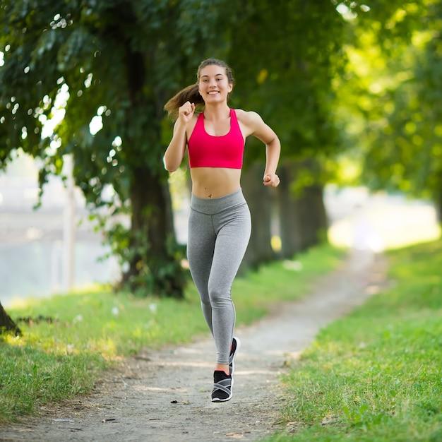 Giovane donna di forma fisica che va in giro nel parco Foto Premium