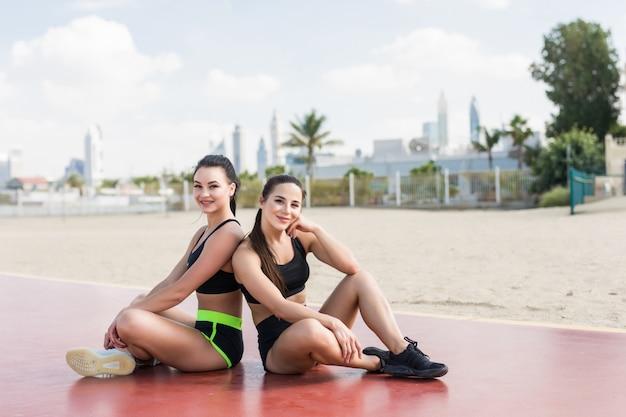Le giovani donne di forma fisica nello sport coprono la seduta sulla spiaggia all'aperto Foto Premium