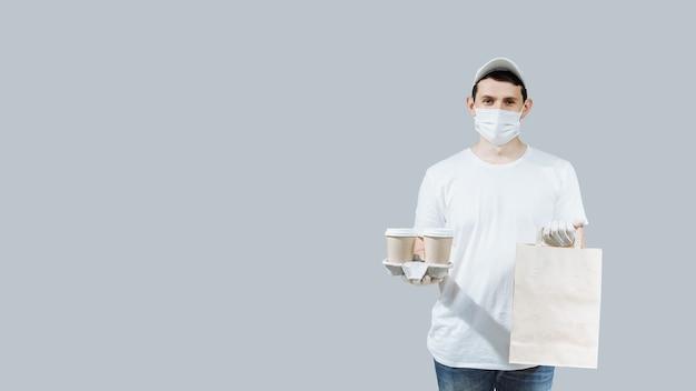 Un giovane addetto alle consegne di cibo con maschera protettiva e guanti tiene in mano scatole di cibo e offre al cliente una consegna rapida di cibo e bevande. Foto Premium