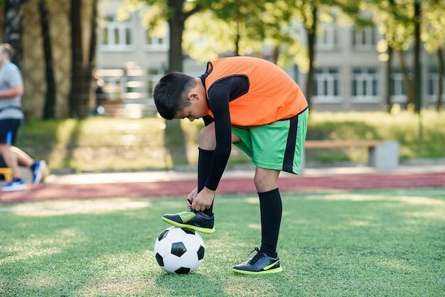 Giovane calciatore che lega i lacci delle scarpe in piedi sulla palla. Foto Premium