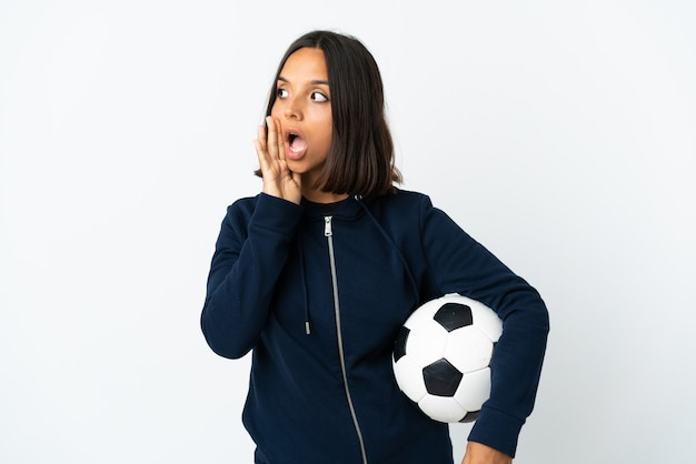 Donna giovane calciatore isolata su bianco che bisbiglia qualcosa con gesto di sorpresa mentre guarda al lato Foto Premium