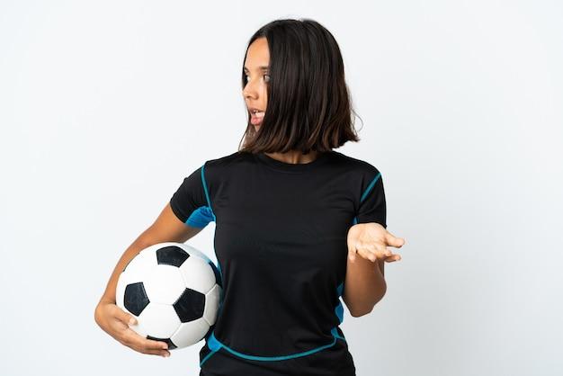 Donna giovane calciatore isolata su bianco con espressione di sorpresa mentre guarda di lato Foto Premium