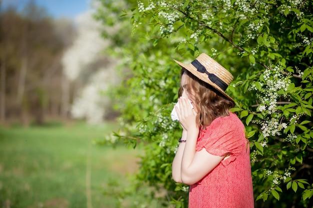 Giovane ragazza che soffia il naso e starnuti nel tessuto davanti all'albero in fiore. allergeni stagionali che colpiscono le persone. la bella signora ha la rinite. Foto Premium