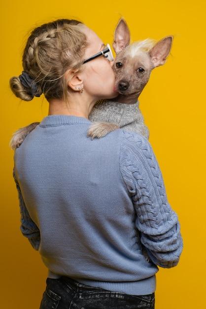 Una giovane ragazza con gli occhiali e un maglione bacia il suo cane crestato cinese su uno sfondo giallo Foto Premium