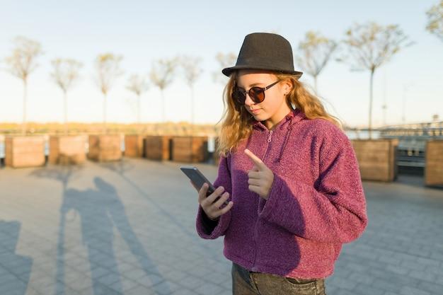 Ragazza che osserva in telefono mobile e che mostra il dito indice in su Foto Premium