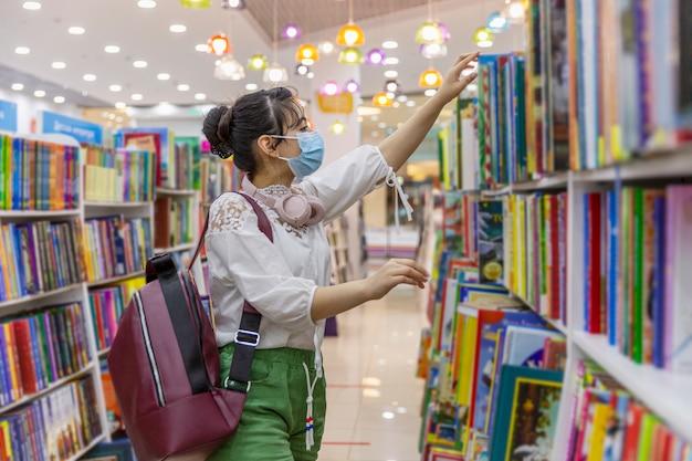 La ragazza in una mascherina medica sceglie un libro in una libreria. conoscenza ed educazione. precauzioni durante la pandemia di coronavirus. Foto Premium