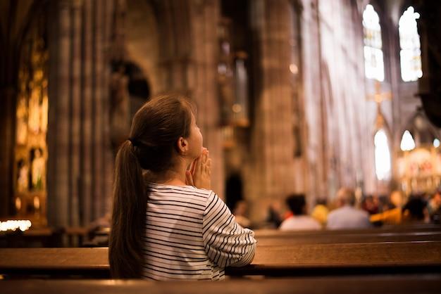 Ragazza che prega nella chiesa che sta sulle sue ginocchia Foto Premium