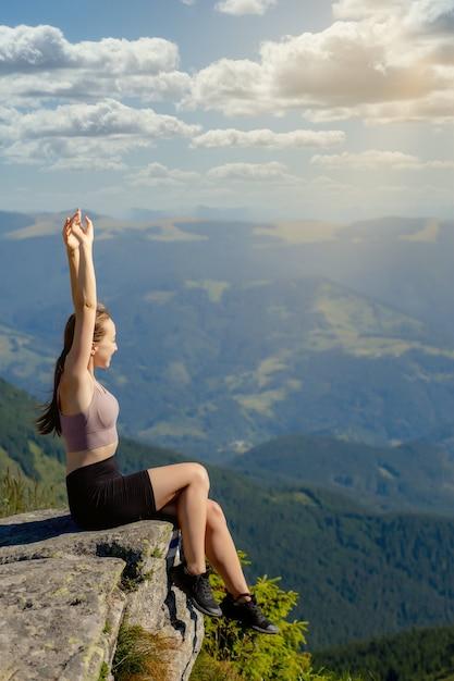La ragazza in cima alla montagna alzò le mani sul cielo blu Foto Premium