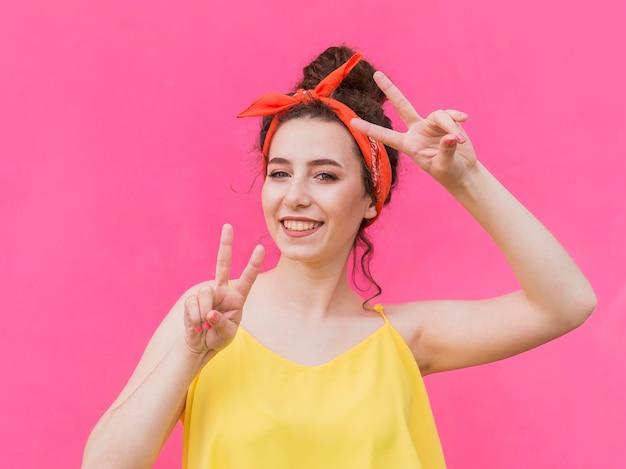 Ragazza con i gesti del segno di pace e della bandana Foto Premium