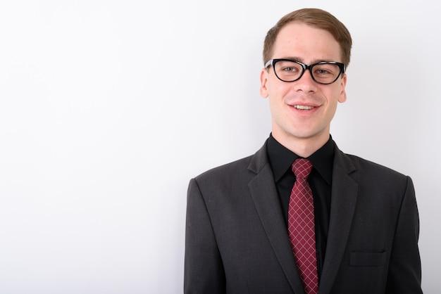 Vestito da portare del giovane uomo d'affari bello sulla parete bianca Foto Premium
