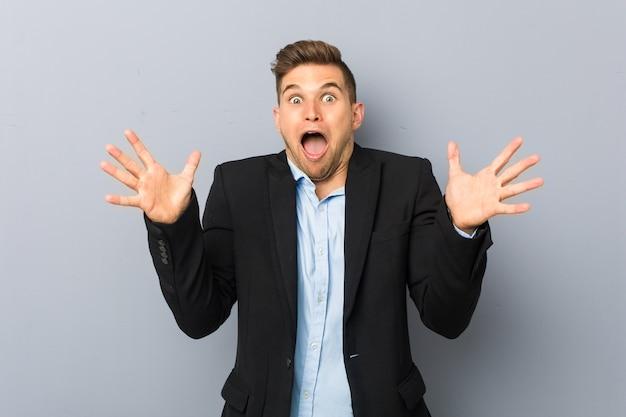 Giovane uomo caucasico bello che celebra una vittoria o un successo, è sorpreso e scioccato. Foto Premium