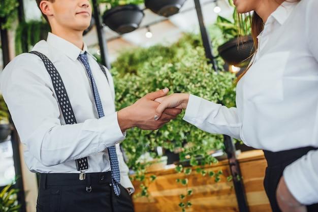 Stretta di mano del giovane datore di lavoro bello con la donna attraente. primo piano, immagine ritagliata. Foto Premium