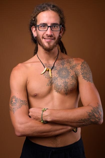 Giovane uomo ispanico bello con i dreadlocks a torso nudo contro br Foto Premium