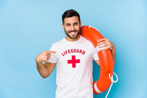 Il giovane uomo bello del bagnino isola la persona che indica a mano uno spazio della copia della camicia, fiero e sicuro Foto Premium